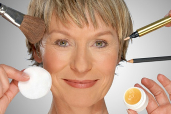 Mature woman surrounded by make-up equipment, portrait