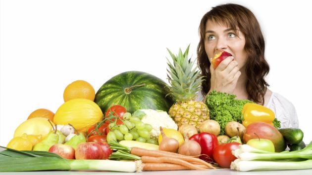 Woman eating an apple with a table full of produce before her.