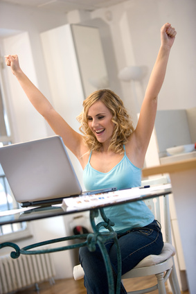 woman at laptop with arms up